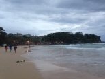 Phuket beach with surfing and restaurants at the end