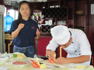 Our tour guide for Halong Bay with the boat's chef - demonstrating the art of food decoration, seen often in Vietnamese food presentation
