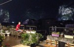 On the rooftop bar, with lit-up karst mountains surrounding the town